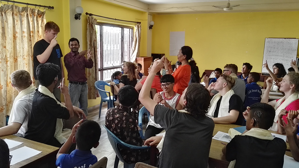 Callum teaching British Sign Language during the Mary Hare School Nepal trip with VoluntEars