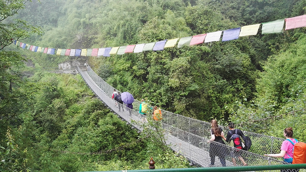 Sophie on a wire bridge in the mountains during the Mary Hare School Nepal trip with VoluntEars
