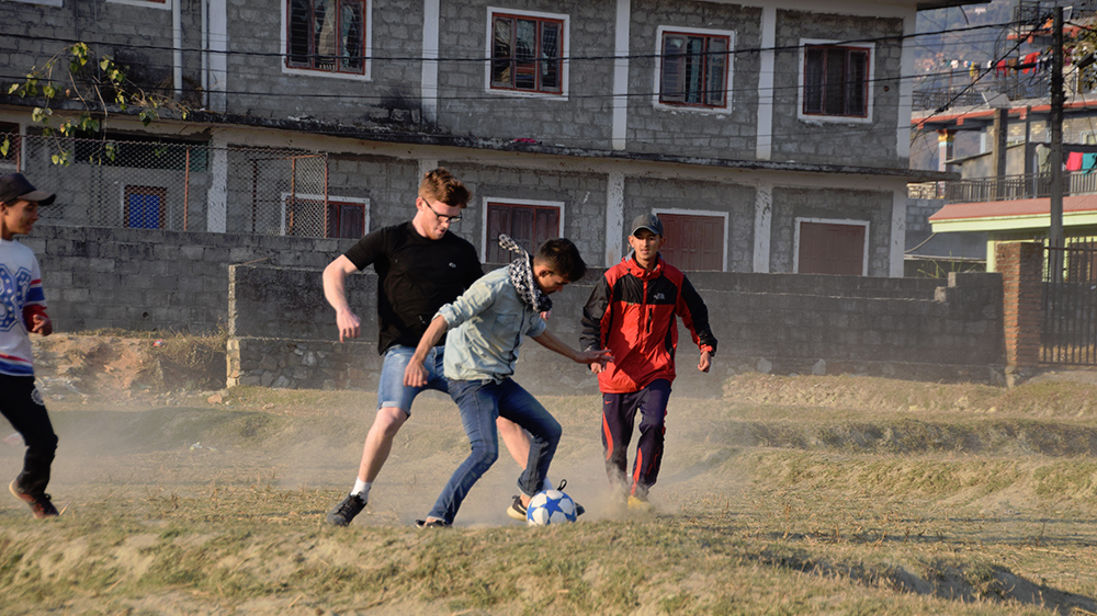 Ben playing football on a dry padi field during his Nepal trip with VoluntEars
