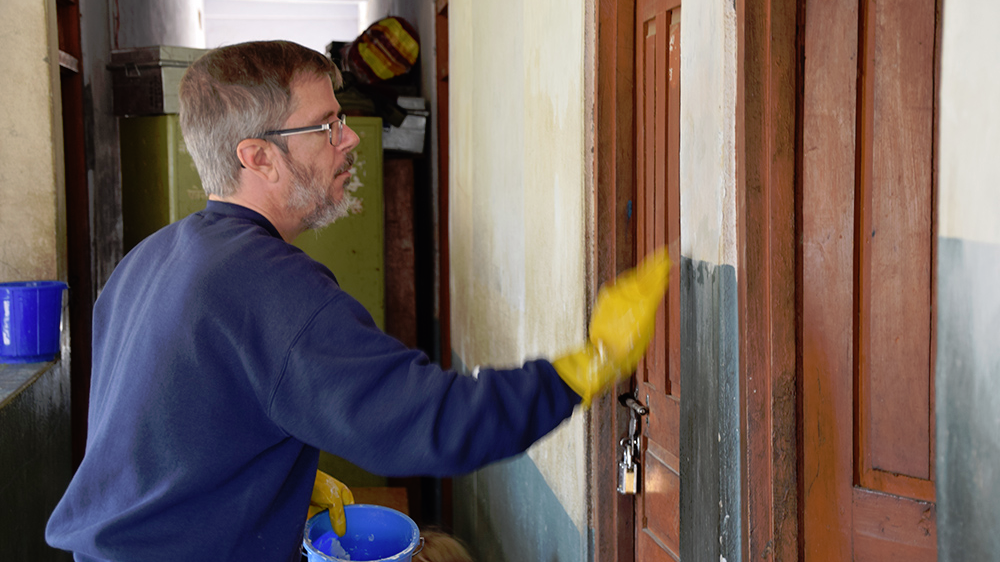 Jerry preparing a wall for painting during his Nepal trip with VoluntEars