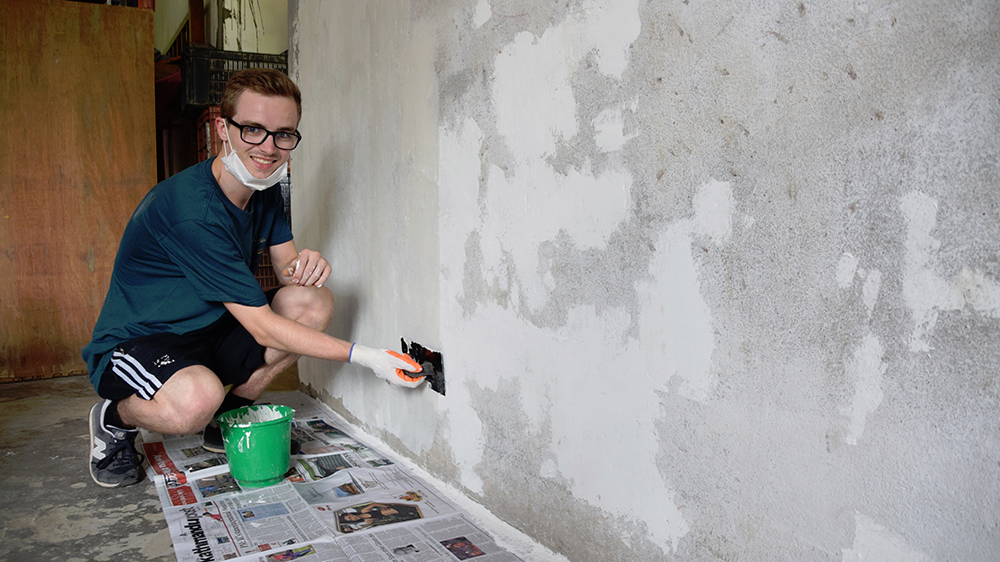 Sam plastering a wall in a Deaf school dormitory during his Nepal trip with VoluntEars