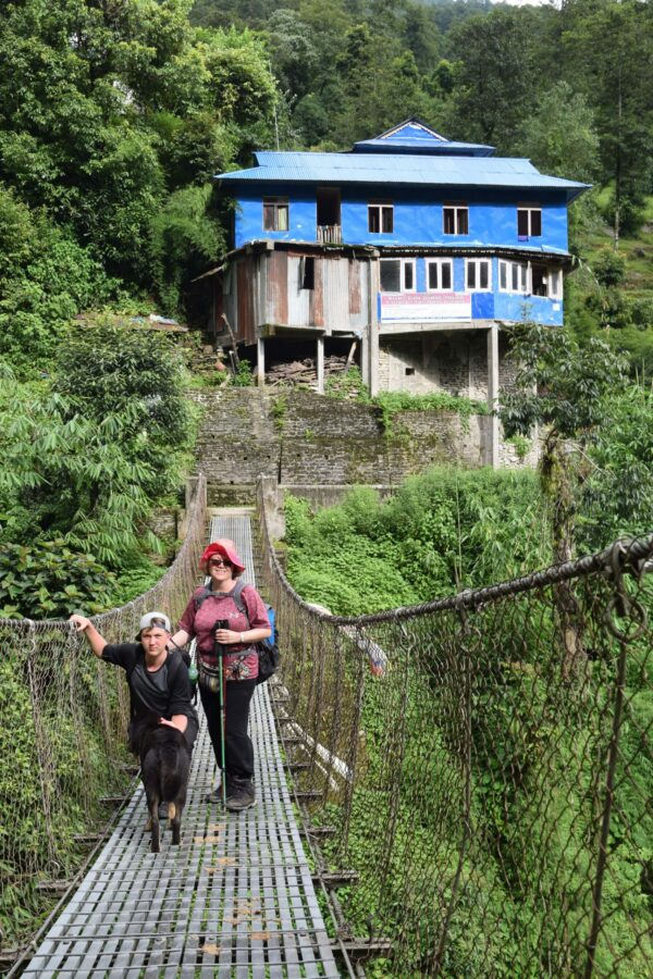 Donna and Noah on a bridge over a river during the trek in the Himalayan mountains with VoluntEars in Nepal