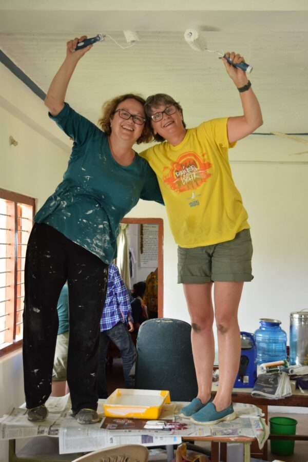 Donna (left) helping to paint the staff room at a Deaf school in Nepal