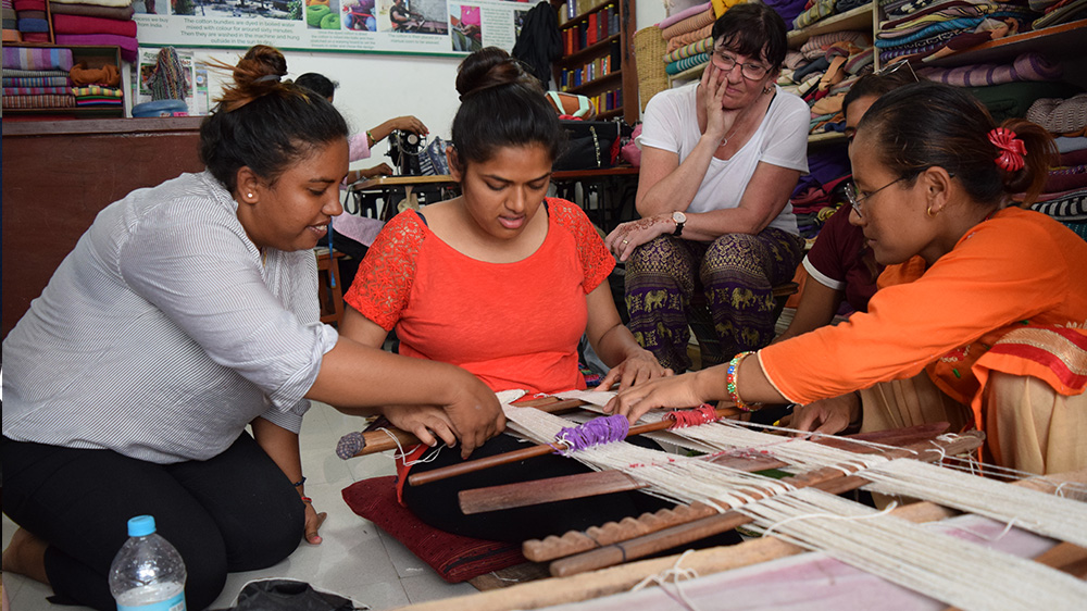 Hiral trying traditional weaving during her Nepal trip with VoluntEars
