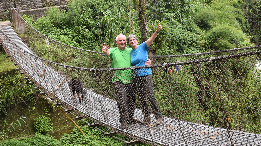 Phil and Shirley on a bridge during the trek on their Nepal trip with VoluntEars