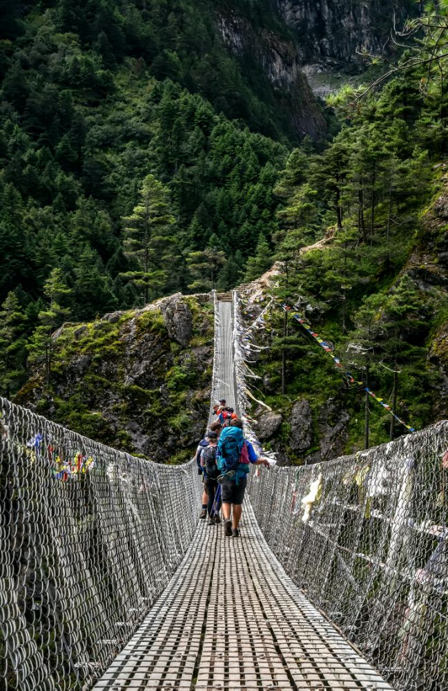 Crossing a bridge in the mountains on the VoluntEars Everest Base Camp trek